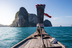 Traditional long tail boat is sailing on Andaman sea in Thailand. Traditional long tail boat is sailing in Andaman sea with a clear blue sky and limestone island Stock Image