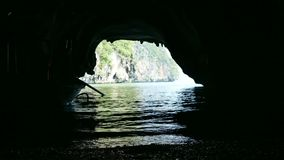 Traditional long tail boat travel in cave stock video