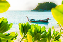 Traditional longtail boat docking in front of the beach in Lipe, Royalty Free Stock Images