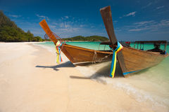 Traditional Longtail Boats Koh Lipe. Two traditional longtail boats parked on a white sand beach surrounded by crystal clear turquoise water on the paradise royalty free stock photo
