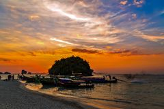 Sunrise longtail boats Krabi, Thailand. Traditional longtail boats, rocks, cliffs, tropical beach. Krabi, Thailand. Beauty Scene or sun over colorful sky with Royalty Free Stock Images