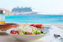 Traditional lunch with delicious fresh greek salad and brusketa served for lunch at outdoor cafe with view on the sea Stock Photography