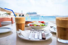 Traditional lunch with delicious fresh greek salad, frappe and brusketa served for lunch at outdoor cafe Royalty Free Stock Photo