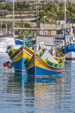 Traditional Luzzu boat at Marsaxlokk harbor in Malta. Traditional Luzzu boat at Marsaxlokk harbor, a fishing village located in the south-eastern part of Malta Stock Image