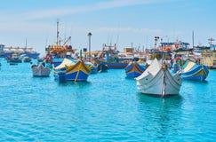 Traditional luzzu boats, Marsaxlokk. Traditional luzzu boats are neighboring with fishing trawlers in Marsaxlokk harbour, Malta stock photography