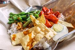 A traditional malay curry paste rice dish nasi lemak. Served on a paper with chips stock photography