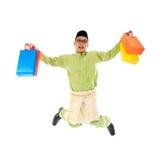 Traditional Malay male shopping and jumping. In joy during hari raya ramadan festival Royalty Free Stock Photo