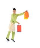 Traditional Malay male shopping and jumping. In joy during hari raya ramadan festival Stock Photo