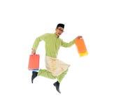 Traditional Malay male shopping and jumping. In joy during hari raya ramadan festival Stock Image