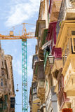 Traditional maltese balconies with construction crane. Traditional wooden balconies warm sunlight with crane in background, Valletta, Malta, June 2016 Stock Photography