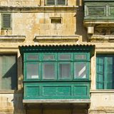 Traditional maltese balcony. Building with traditional colorful maltese balcony in historical part of Valletta. Windows on the facade of a house in Malta Stock Photography