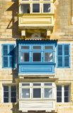 Traditional maltese balcony. Building with traditional colorful maltese balcony in historical part of Valletta. Windows on the facade of a house in Malta Stock Photo