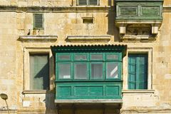Traditional maltese balcony. Building with traditional colorful maltese balcony in historical part of Valletta. Windows on the facade of a house in Malta Stock Images