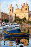 Traditional maltese boat Luzzu moored in the harbor in front of. The traditional maltese boat Luzzu and yachts moored in the harbor of Dockyard creek in front of Royalty Free Stock Images