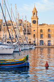 Traditional maltese boat Luzzu and yachts moored in the harbor. The traditional maltese boat Luzzu  and yachts moored in the harbor in Dockyard creek in front of Stock Photo