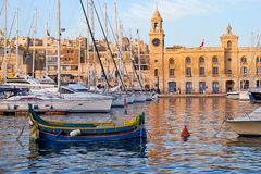 Traditional maltese boat Luzzu and yachts moored in the harbor. The traditional maltese boat Luzzu  and yachts moored in the harbor in Dockyard creek in front of Royalty Free Stock Photos