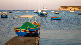 Traditional Maltese boat. At pier. Several other boats nearby. Ripples on water, purple sky and distant cliff. Was taken in Malta, Marsaskala Stock Photography