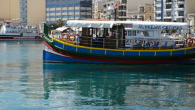The traditional Maltese boat for tourists cruises. SLIEMA, MALTA - APRIL 22: The traditional Maltese boat for tourists cruises on April 22, 2015 in Sliema, Malta stock video footage