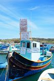 Protest boat in Marsaxlokk harbour, Malta. Traditional Maltese Dghajsa fishing boat in the harbour with protests against MAF, Marsaxlokk, Malta, Europe Royalty Free Stock Photos