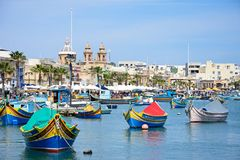 Pretty Maltese fishing harbour, Marsaxlokk. Traditional Maltese Dghajsa fishing boats in the harbour with the parish church of Our Lady of Pompei to the rear Stock Image