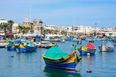 Fishing harbour and waterfront, Marsaxlokk. Traditional Maltese Dghajsa fishing boats in the harbour with the parish church of Our Lady of Pompei to the rear Stock Photography