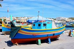 Maltese Dghajsa boats on Marsaxlokk quayside. Traditional Maltese Dghajsa fishing boats in the harbour with town buildings to the rear, Marsaxlokk, Malta Royalty Free Stock Photo