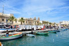Marsaxlokk waterfront, Malta. Traditional Maltese Dghajsa fishing boats in the harbour with waterfront buildings and market stalls to the rear, Marsaxlokk Stock Photography