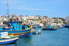 Fishing boats in the harbour, Marsaxlokk, Malta. Traditional Maltese Dghajsa fishing boats in the harbour with waterfront buildings to the rear, Marsaxlokk Stock Photography