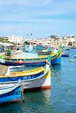 Fishing boats in Marsaxlokk harbour, Malta. Traditional Maltese Dghajsa fishing boats in the harbour with waterfront buildings to the rear, Marsaxlokk, Malta Royalty Free Stock Image