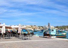 Marsaxlokk harbour and pavement cafes, Malta. Traditional Maltese Dghajsa fishing boats in the harbour with waterfront buildings to the rear and restaurants on Stock Photo