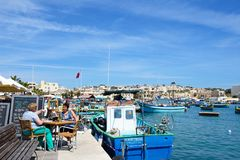 Marsaxlokk harbour and quayside, Malta. Traditional Maltese Dghajsa fishing boats in the harbour with waterfront buildings to the rear and two women relaxing at Royalty Free Stock Photos