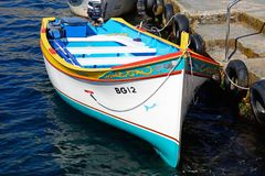 Traditional Maltese Dghajsa water taxi, Malta. Traditional Dghajsa water taxi boat moored at the departure point in the bay, Blue Grotto, Malta, Europe Stock Image