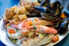 Maltese seafood and fish platter. Traditional maltese fish and seafood platter set mix of calamari rings in tempura, giant shrimps, clams, fish fillets and Royalty Free Stock Photography