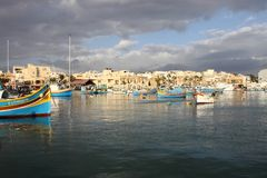 Traditional maltese fishing boat in Marsaxlokk. Marsaxlokk, Malta - January 21, 2018: Luzzu anchored in Malta, at the port of Marsaxlokk, a traditional fishing Stock Photo