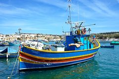 Traditional Maltese fishing boat, Marsaxlokk. Traditional Maltese fishing boats and Dghajsa boats in the harbour with waterfront buildings to the rear Royalty Free Stock Photography