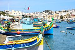 Traditional Maltese fishing boats, Marsaxlokk. Traditional Maltese Dghajsa fishing boats in the harbour with waterfront buildings to the rear, Marsaxlokk, Malta Stock Images