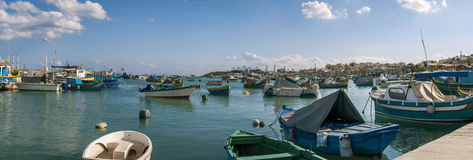 Traditional Maltese fishing boats. Panoramic view to the fishing boats in Marsaxlokk village Stock Images