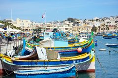Traditional Maltese fishing harbour, Marsaxlokk, Malta. Traditional Maltese Dghajsa fishing boats in the harbour with waterfront buildings to the rear Royalty Free Stock Photos