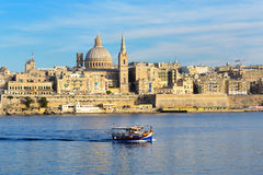 The traditional Maltese Luzzu boat for tourists cruises. And view on Valletta, Sliema, Malta Royalty Free Stock Photo