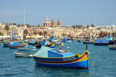 Maltese Luzzu fishing boats Malta. Traditional Maltese Luzzu fishing boats in Marsaxlokk Harbor. Mediterranean island of Malta. March 2013 Royalty Free Stock Images