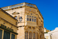 Traditional maltese townhouse. Victoria, Malta - March 9 2017: Traditional maltese townhouse built of limestone with wooden balcony and sterling jewelry shop in Royalty Free Stock Photo