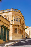 Traditional maltese townhouse. Victoria, Malta - March 9 2017: Traditional maltese townhouse built of limestone with wooden balconyand sterling jewelry shop in Stock Photos