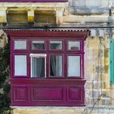 Traditional maltese window. Building with traditional maltese window decorated with fresh flowers Stock Photography