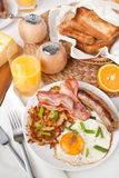 Traditional Manhattan brunch. With Sausage, Bacon, Fried Egg, Hashbrowns and Orange Juice Royalty Free Stock Photos