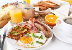 Traditional Manhattan brunch. Toast, Fried Eggs, Hashbrowns, Sausages, Jam and Coffee Royalty Free Stock Photos