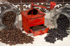 Traditional manual coffee grinder beside different types of coffee beans Royalty Free Stock Photos