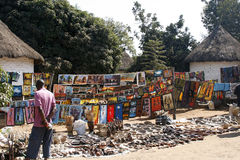 Traditional Market for African Crafts. Colorful African crafts on display at a traditional market in Zambia. Mostly handmade wooden crafts and drawings stock photography