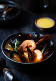 Traditional Marseille Bouillabaisse fish soup with prawns, mussels tomato, lobster, squid. Black background. Stock Images