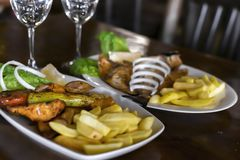 Traditional Mediterranean food. Two dishes on the table in the restaurant. Baked fish and barbecue with vegetable garnish.  stock images