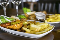 Traditional Mediterranean food. Two plates and glasses on the table in the restaurant. Baked fish and barbecue with vegetable. Garnish stock photos